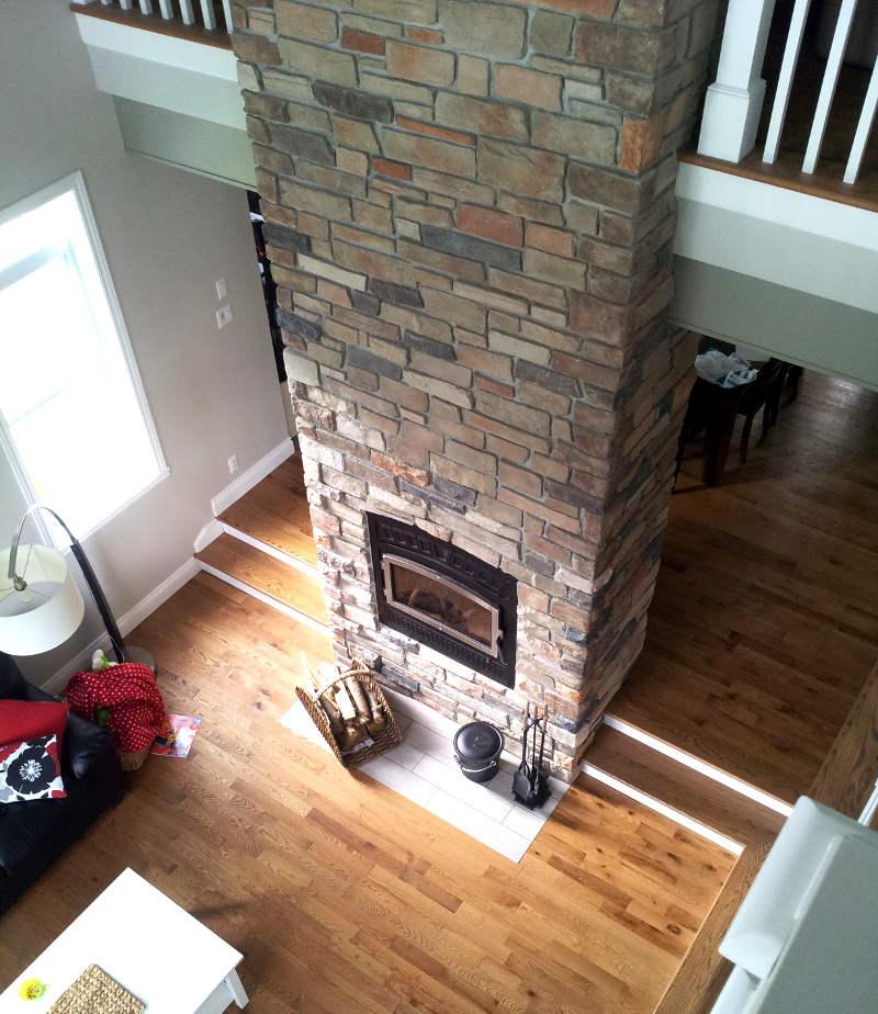 Foyer central avec manteau de cheminée en pierre jusqu'au plafond